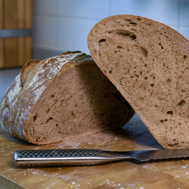 """Artisan sourdough bread cut open on a cutting board with serrated knife in front"" stock image"