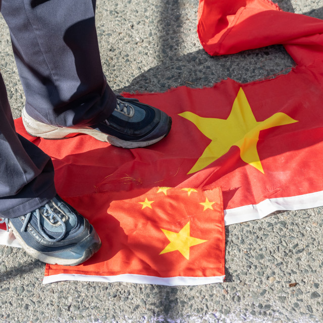 """""""Man Stepping On Ripped-up Chinese Flags"""" stock image"""