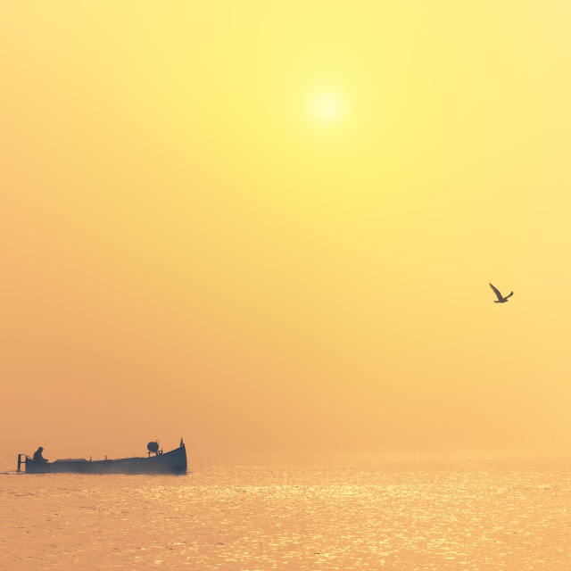 """""""Fishing boat sailing in the sea during golden foggy morning. Bea"""" stock image"""