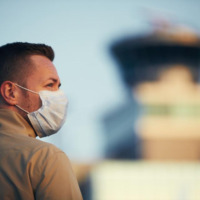 """Man wearing face mask at airport"" stock image"