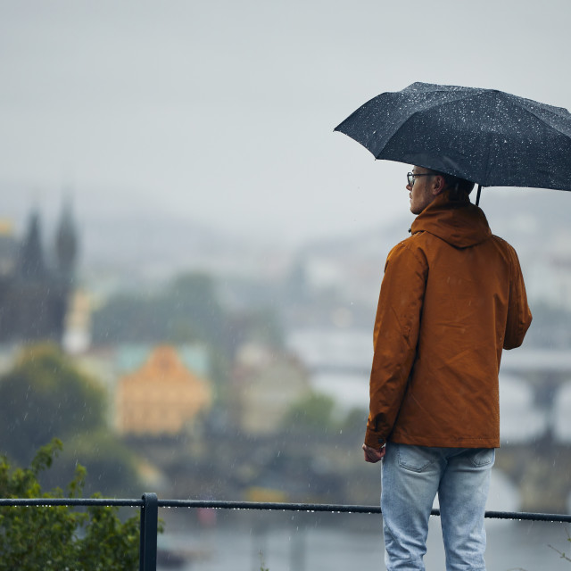 """""""Man with umbrella during rain in city"""" stock image"""