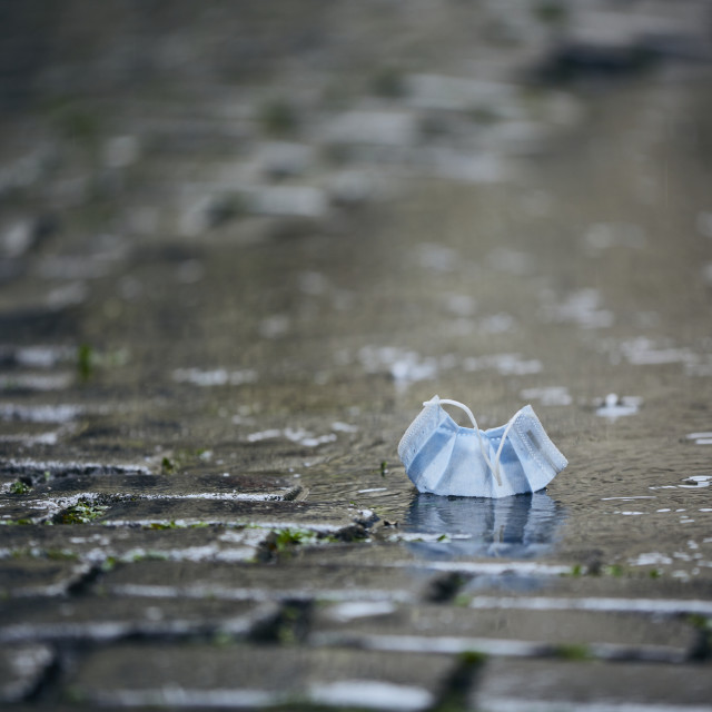 """""""Used face mask in puddle during rain"""" stock image"""