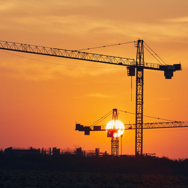 """""""Building activity on contruction site at sunrise"""" stock image"""