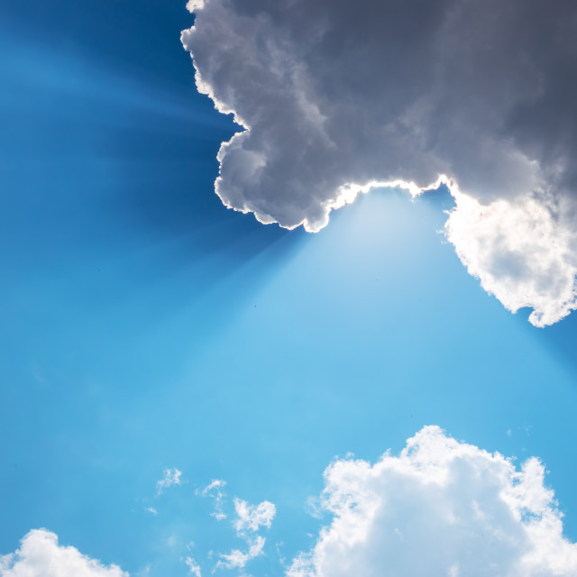 """Sun, sunbeam and clouds in blue sky"" stock image"