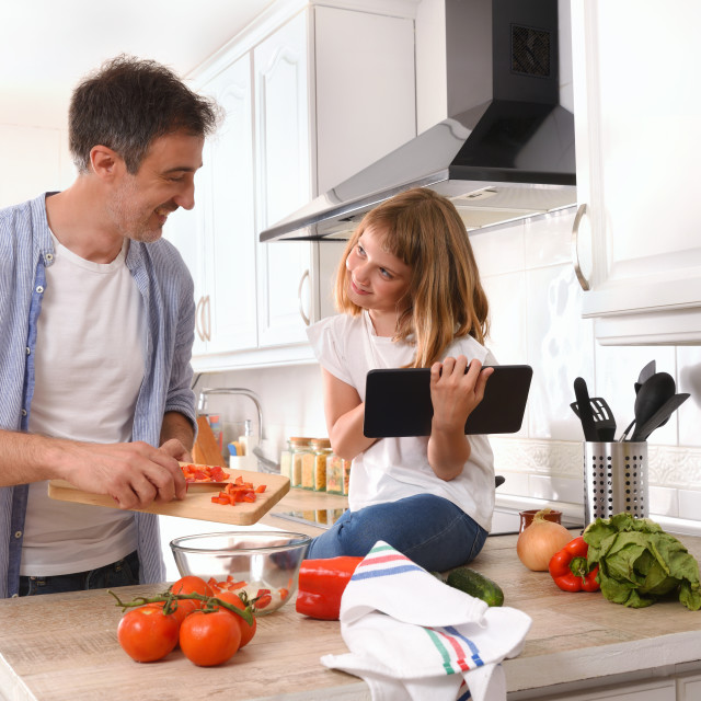 """""""Happy father and daughter looking knowingly cooking with tablet"""" stock image"""
