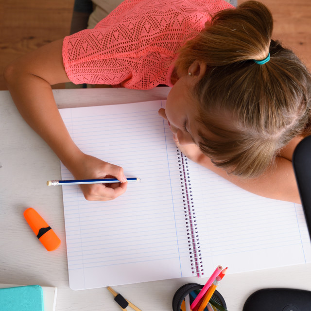 """""""Little girl studying writing in notebook on desk top"""" stock image"""