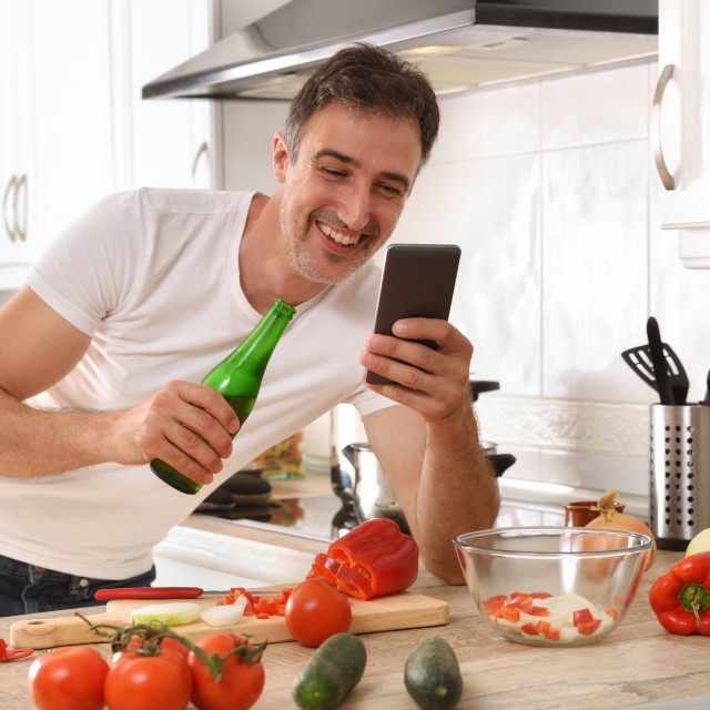 """""""Man looking at mobile phone with beer while cooking detail"""" stock image"""
