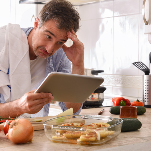 """""""Novice chef looking at a tablet with strange face"""" stock image"""