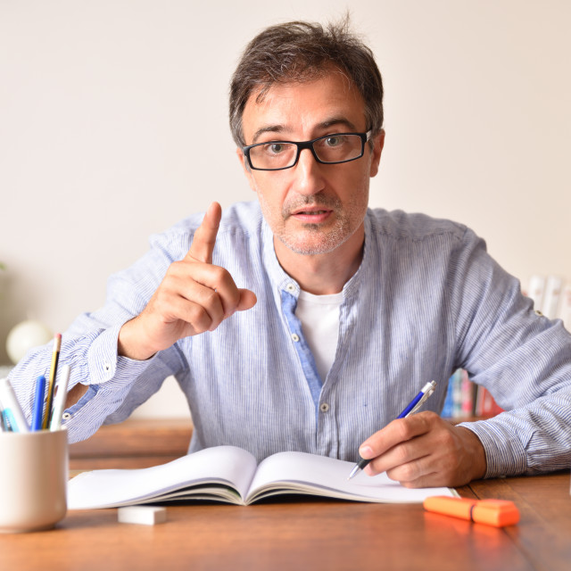 """""""Serious tutor with raised finger writing in a book"""" stock image"""