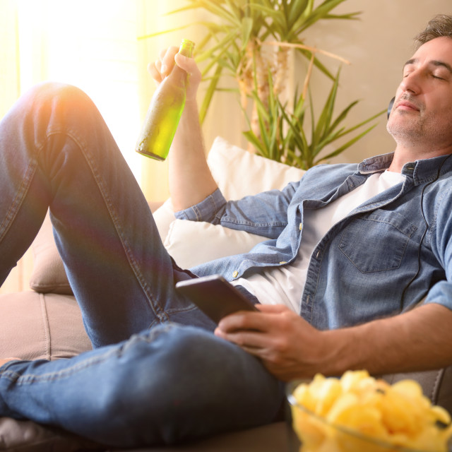 """""""Relaxed man listening to music with headphones with beer home"""" stock image"""