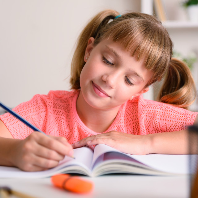 """""""Smiling little girl studying in her room at home"""" stock image"""