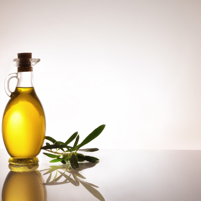 """""""Glass container with oil and olive twig backlit on table"""" stock image"""