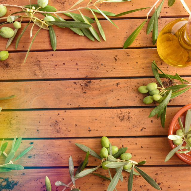 """""""Olive branches filled with olives on wooden table with oil"""" stock image"""