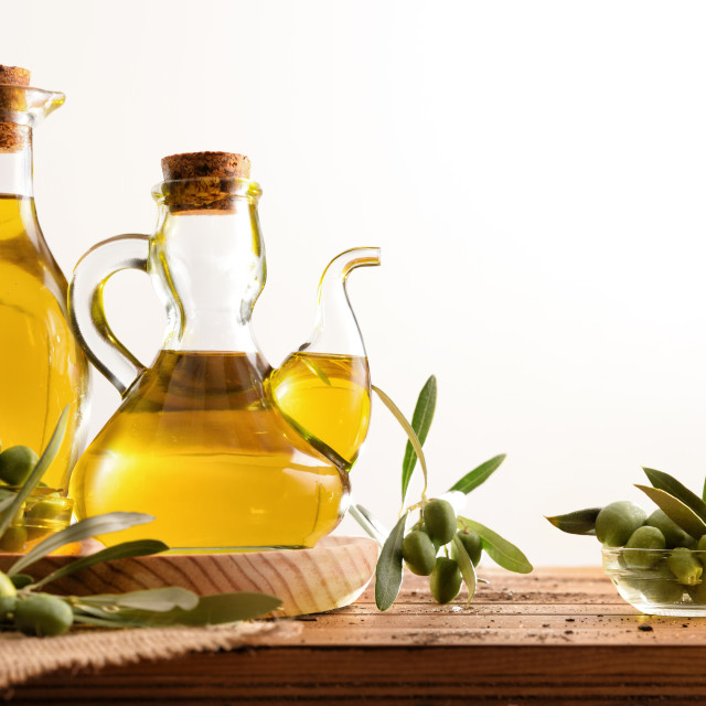 """""""Olive oil dispensers on wooden table with olives isolated white"""" stock image"""