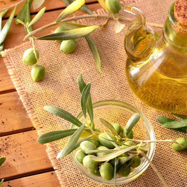 """""""Olive oil on table with branches and olives elevated view"""" stock image"""