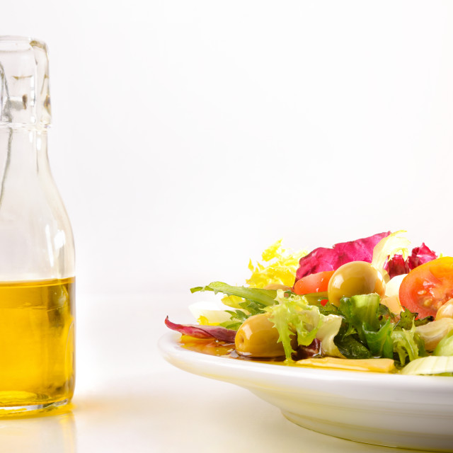"""""""Prepared salad on plate with bottle of oil on white"""" stock image"""