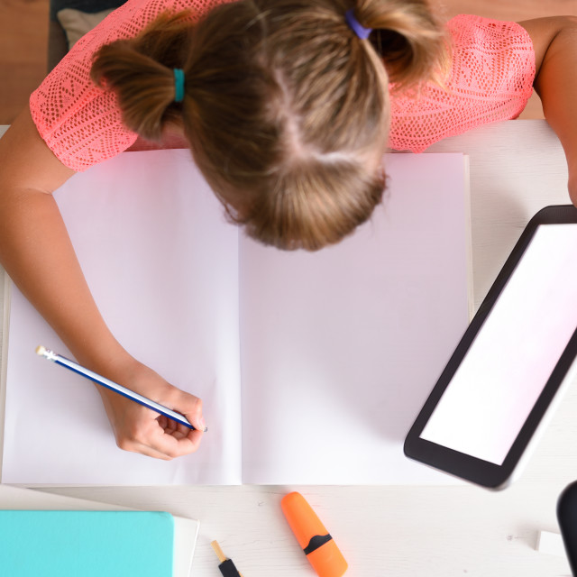 """""""Girl studying at home taking distance lessons with tablet top"""" stock image"""