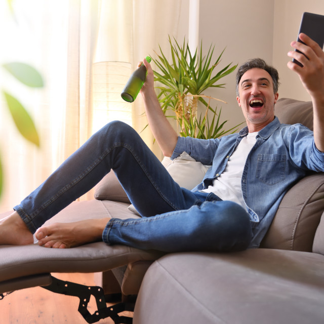"""""""Happy man resting at home with a beer using mobile"""" stock image"""