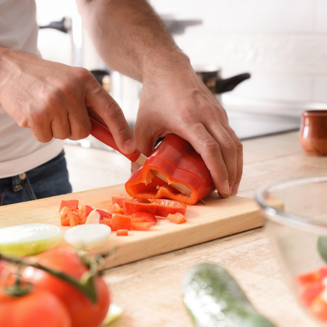 """""""Hands cutting a pepper on cutting board on kitchen bench"""" stock image"""