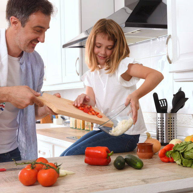 """""""Happy father and daughter preparing vegetables in the kitchen"""" stock image"""