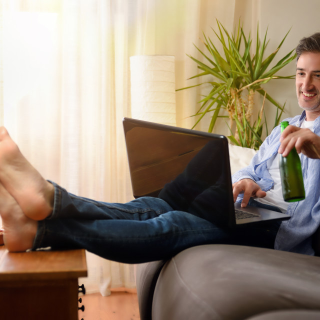 """""""Man having a snack sitting on a sofa using laptop"""" stock image"""