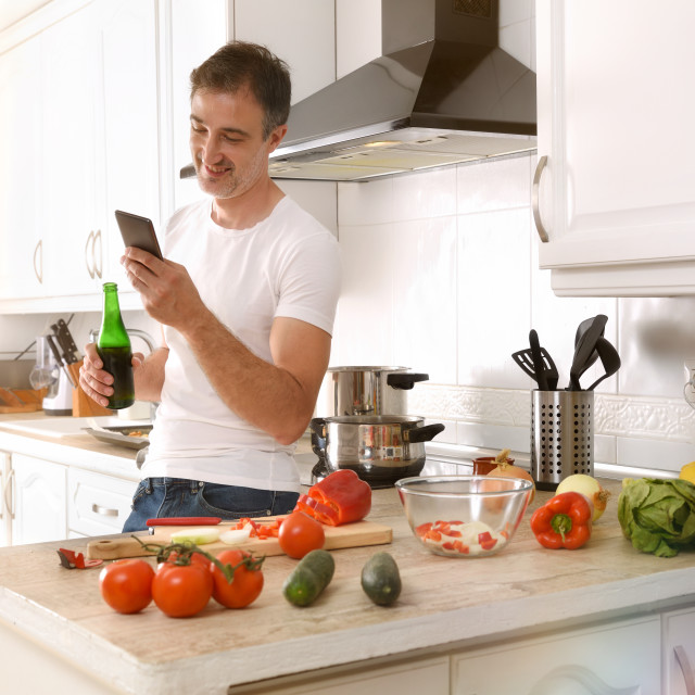 """""""Man looking at mobile phone with beer while cooking"""" stock image"""
