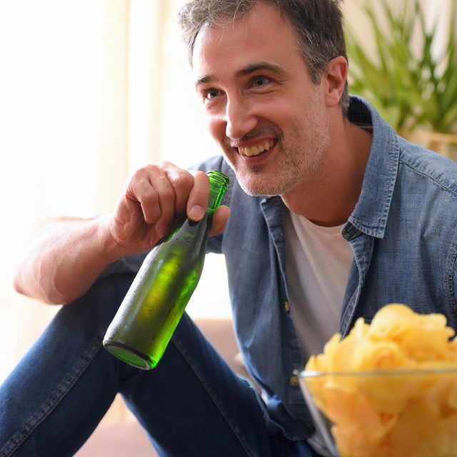 """""""Man smiling having a beer snack at home close up"""" stock image"""