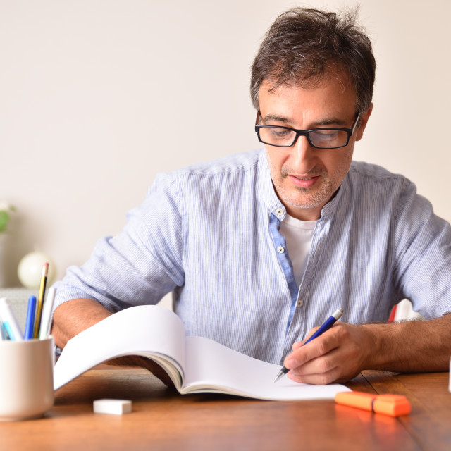 """""""Smiling adult man tudying on wooden table underlining in book."""" stock image"""