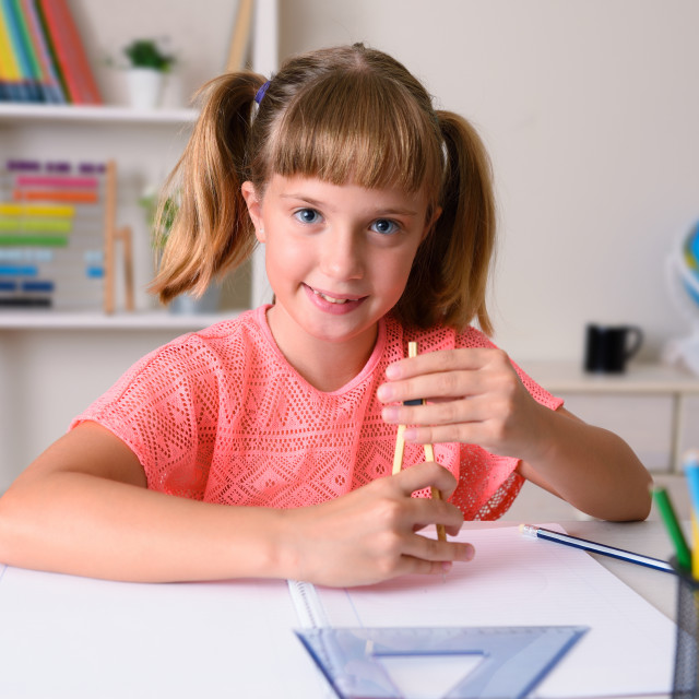 """""""Smiling girl doing class work with a compass at home"""" stock image"""