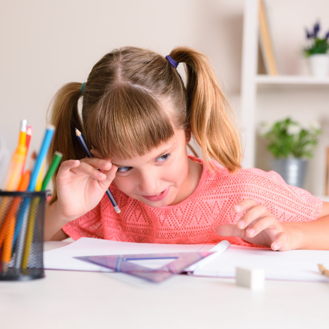 """""""Smiling girl doing homework at home with hand on forehead"""" stock image"""