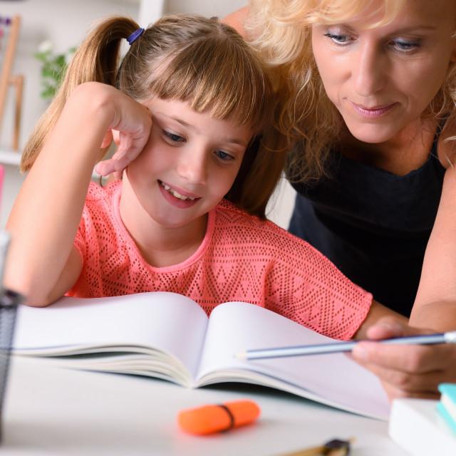 """Teacher explaining lesson to girl studying at home"" stock image"
