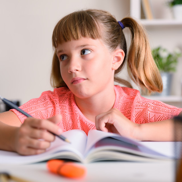 """""""Tired girl studying school assignments at home"""" stock image"""