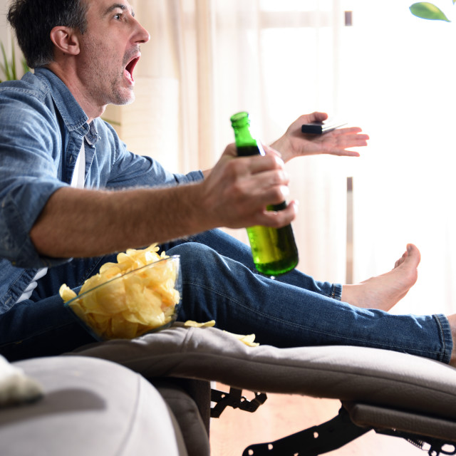 """""""Angry man watching sports on television sitting on sofa"""" stock image"""