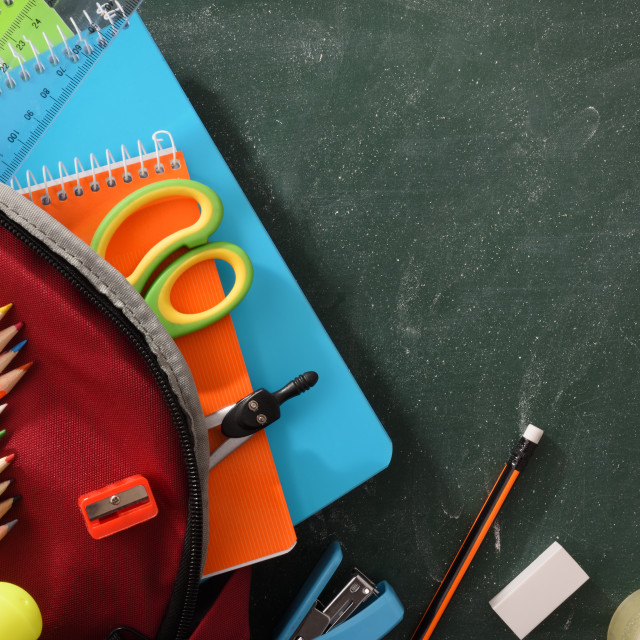 """Backpack full of school supplies on green blackboard detail top"" stock image"