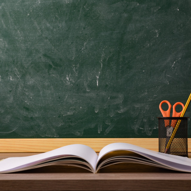 """""""Empty green class blackboard and desk with book and supplies"""" stock image"""