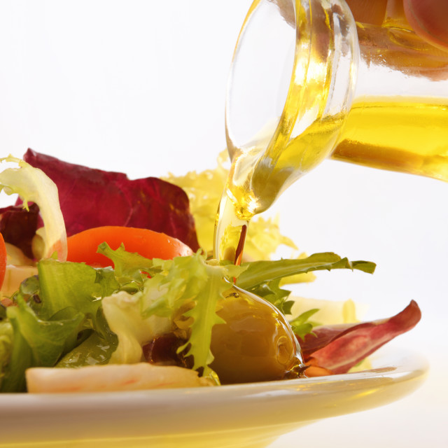 """""""Pouring olive oil from oil dispenser on salad close up"""" stock image"""