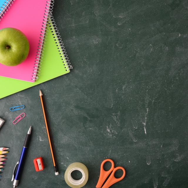 """School supplies on green blackboard top view"" stock image"