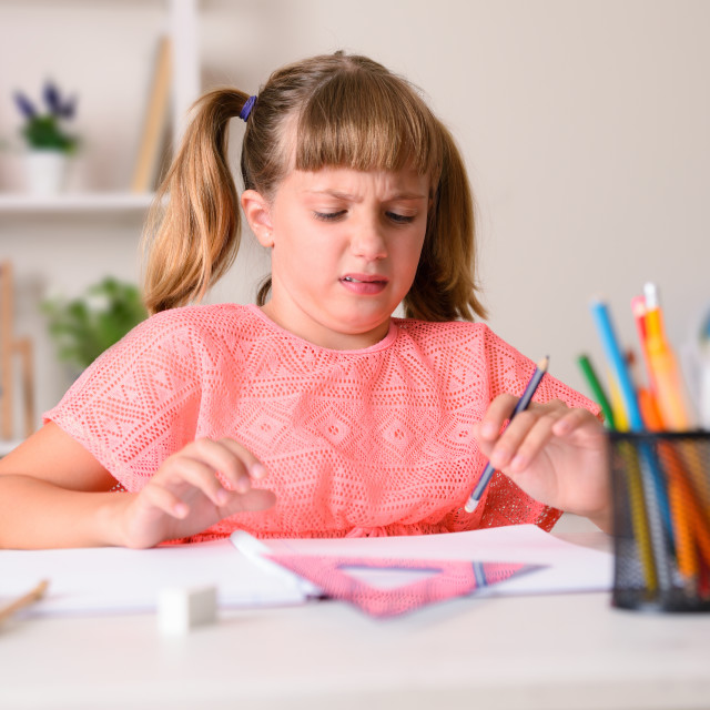 """""""Girl with disgusted face doing schoolwork at home desk"""" stock image"""