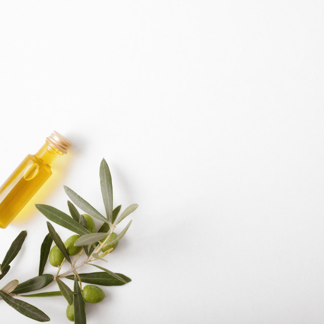 """""""Jar with oil and olive twig on white table top"""" stock image"""