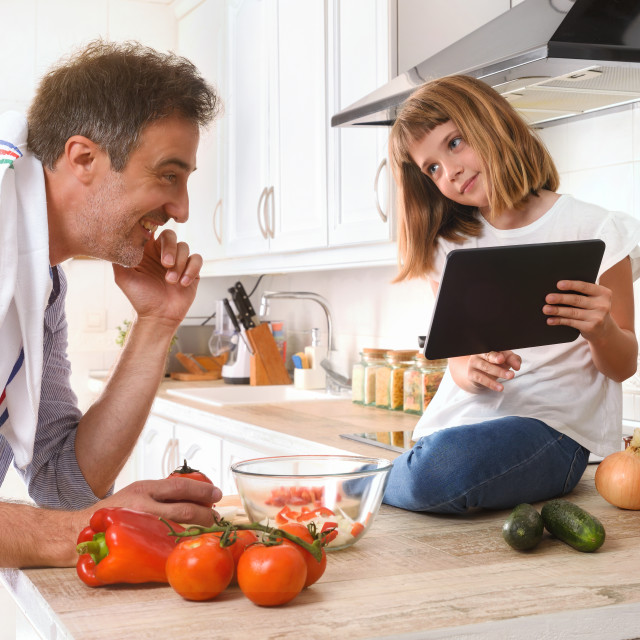 """""""Girl showing her father a digital recipe from a tablet"""" stock image"""