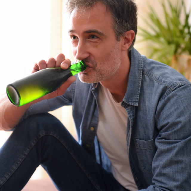 """""""Man drinking from a bottle of beer at home"""" stock image"""