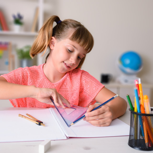 """""""Smiling girl working with a ruler at home"""" stock image"""