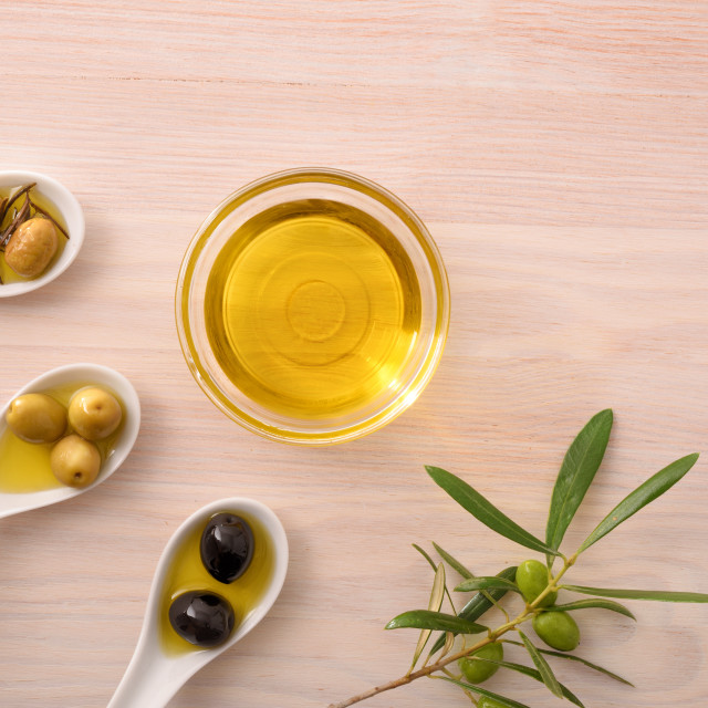 """""""Assortment of olives and oil in bowl on bench top"""" stock image"""