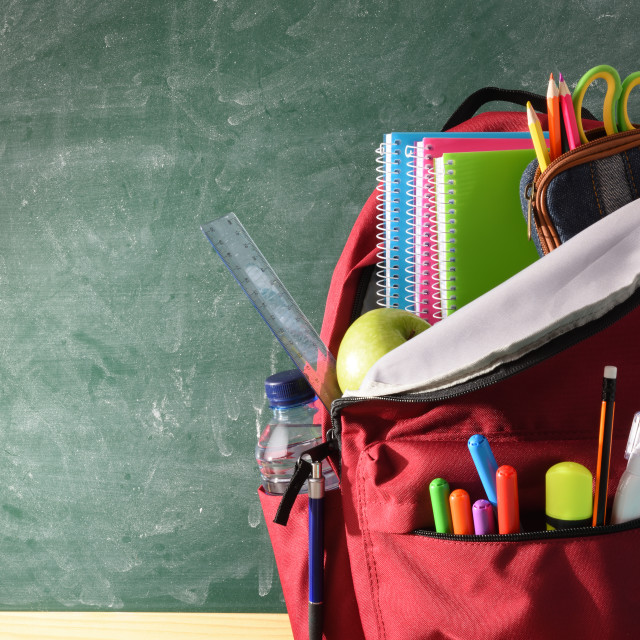 """""""Backpack full of school supplies and blackboard front view detail"""" stock image"""