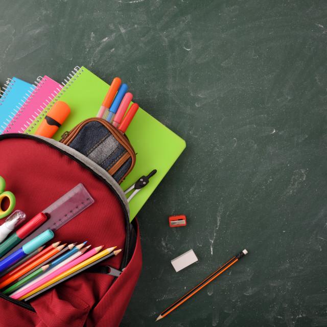 """Backpack full of school supplies on green blackboard top view"" stock image"
