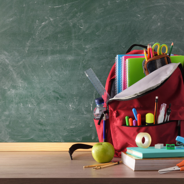 """""""Backpack full of school supplies on table and blackboard front"""" stock image"""
