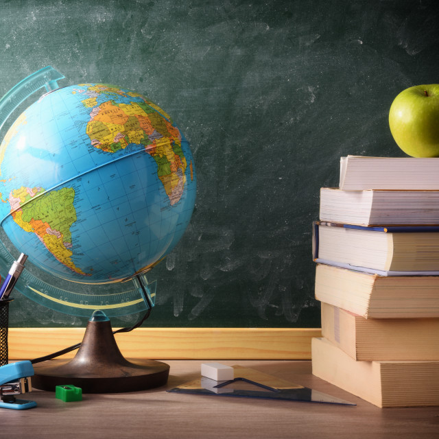 """""""Books and school supplies on classroom desk with blackboard background"""" stock image"""