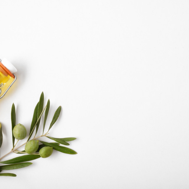 """""""Bottle with oil and olive twig on white table top"""" stock image"""