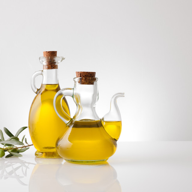"""""""Containers with oil and olive twig on white table front"""" stock image"""