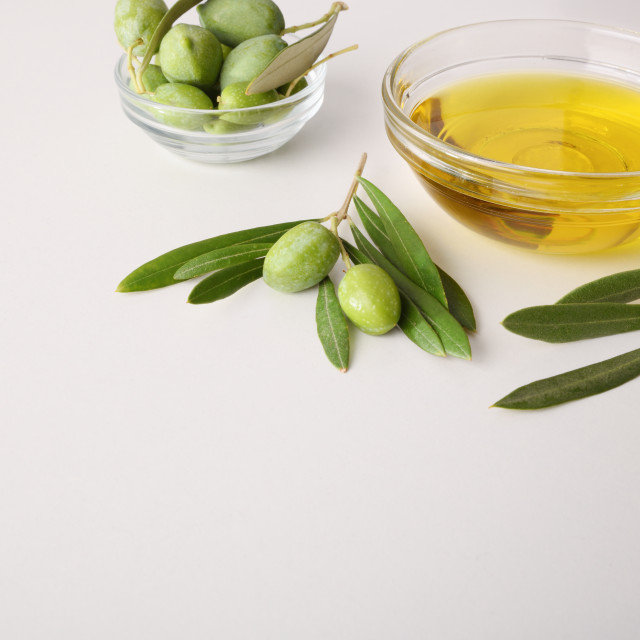 """""""Bowls with oil and olives on white table detail elevated"""" stock image"""